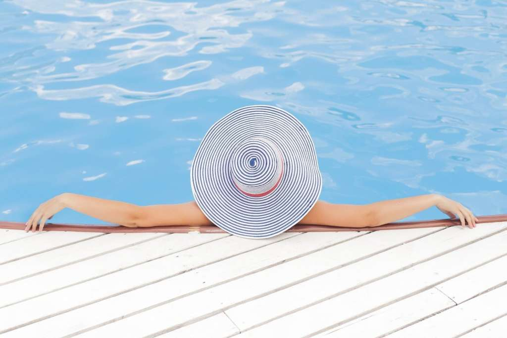 holistic health principles - lady relaxing in pool - stress relief and relaxation