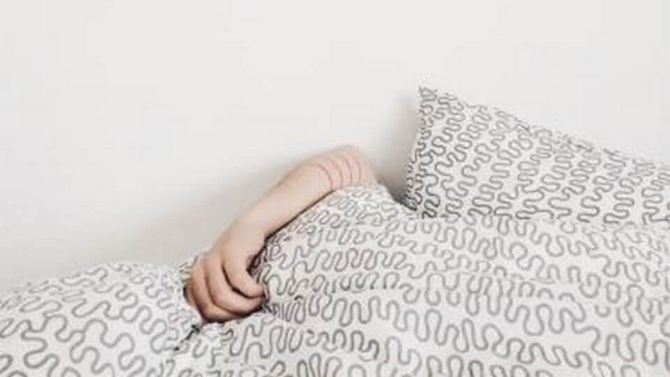factors affecting sleep and how to get deep sleep-person under covers with arm poking out