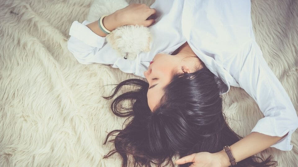 factors affecting sleep and how to get deep sleep-woman and puppy sleeping on bed