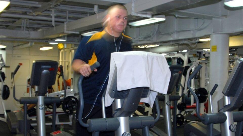 Low impact cardio machines-elliptical-man working out